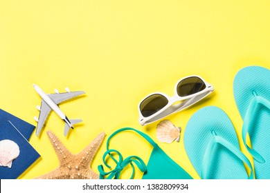 Beach cloth and accesories. Blue flip flops, swimsuit, sunglasses and starfish on yellow background. Top view.