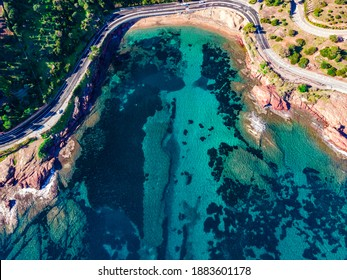 Beach and Coastline French Riviera Côte d'Azur turquoise colour water with red rocks, Roche rouge alongside a road in the village of Agay, close to Cannes