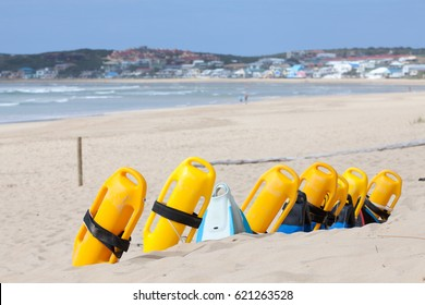 Beach with colorful lifesaving flotation devices, sea and town in background