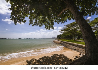 Beach and a concrete sidewalk with trees at the East Coast Park in Singapore.
