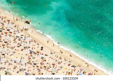 beach of the Cote d'Azur with tourists, sunbeds and umbrellas on the hot summer day. french riviera, Provence, France