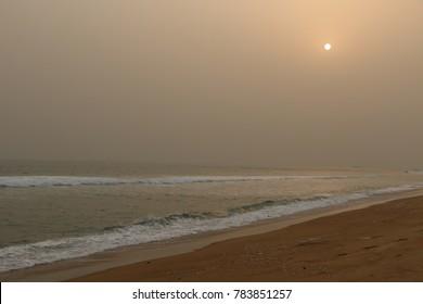 Beach at Cotonou Benin sunsets in foggy sky