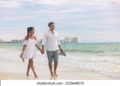 Beach couple romantic sunset walk Asian woman and Caucasian man relaxing walking on Florida vacation beach travel holidays wearing white dress and linen clothes. Happy interracial relationship.