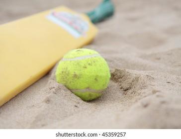 A beach cricket bat with tennis ball on the sand.