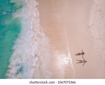Beach drone view Seychelles tropical island, white beach with waves, couple lay down on the beach man and woman