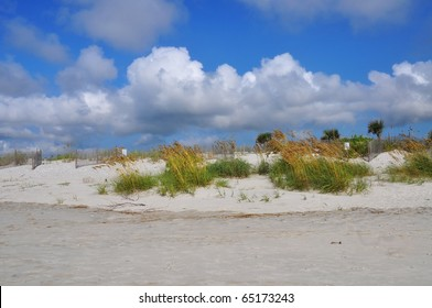 Beach dune with puffy white cloudy sky
