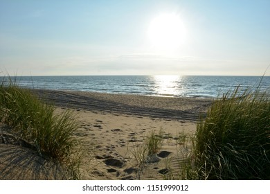Beach with dunes, marsh grass and wooden stages on the North Sea at sunset