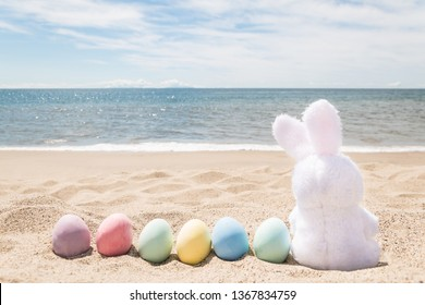 Beach Easter background with bunny and color eggs near ocean