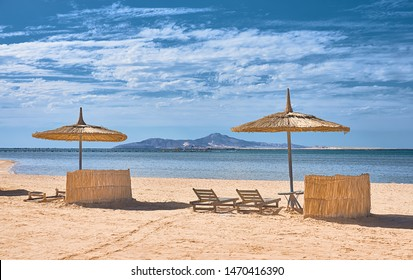 Beach in Egypt with umbrellas, deck chairs and red sea and mountain views.  Egypt resort in Sharm el Sheikh.