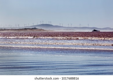 Beach of Essaouira with turbines in the background in Morocco