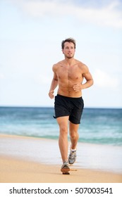 Beach fitness man runner running training cardio. Healthy lifestyle male athlete doing exercise living an active life working out on sunset beach with ocean background topless in shorts.