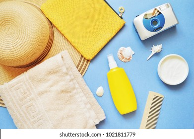 Beach flat lay accessories. Sun hat, beige towel, yellow cosmetic bag, camera, cream, sunscreen bottle, comb and seashells. Summer travel holiday concept
