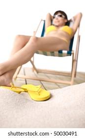 Beach - Flip-flop on sand, woman in yellow bikini on deck chair in background