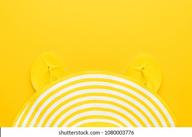 beach flip-flops and hat on the yellow background with copy space. summer concept