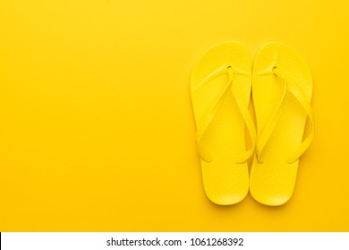 beach flip-flops on the yellow background with copy space. summer is concept