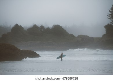 Beach in fog with surfer in waves