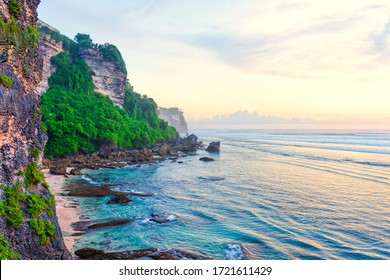 Beach at the foot of the cliff.  Scenic view of a secluded rocky beach before sunset. Bali, Indonesia.