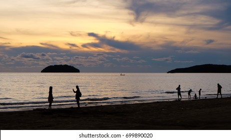 A beach front during sunset, with silhouette of people playing at the beach and enjoying the view. Distant islands in the background. Colorful orange sky with clouds.