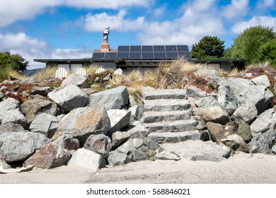 Beach front house with solar panels on the roof, seen in the background behind boulders and stone steps leading up from the sand. Renewable energy