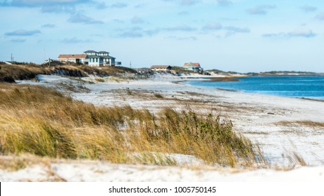Beach Front Houses at the coast of North Carolina with sand, sea grass and ocean in the foreground.