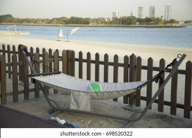 Beach furniture, white bed, wooden fence background