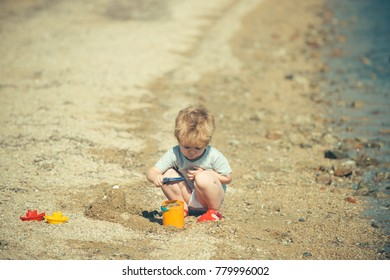 Beach game with sand. Cute boy is playing near sea or ocean with bucket and shovel, builds sand castles. Childhood and happy summer, seaside holidays