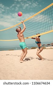 beach games. Beach volleyball concept. Couple have fun playing volleyball. Young sporty active couple beat off volley ball, play game on summer day. Woman and man fit, strong, healthy, doing sport on