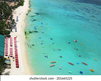 Beach in Guam island, USA, Pacific ocean, air view, transparent turquoise water of bay, many boats and sunbeds, white sand, tropic scene