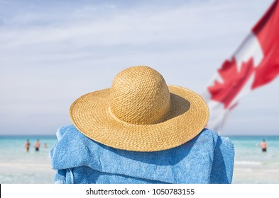 Beach hat and blue towel facing blue sea with Canadian flag in sight, Canadian going on vacation concept