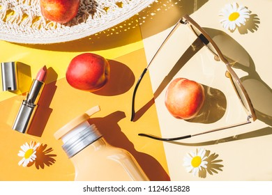 Beach hat, bottle with cream sunglasses, peaches, lipstick, chamomile flowers on a colorful background.