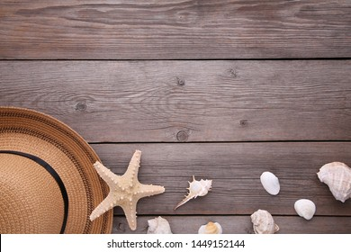 Beach hat with seashells on grey wooden table, frame