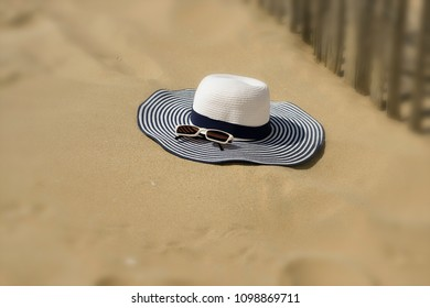Beach hat with sunglasses is in the sand