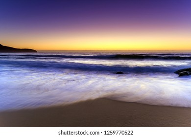 Beach, Headland and glowing Dawn Seascape - Capturing the sunrise from Killcare Beach on the Central Coast, NSW, Australia.