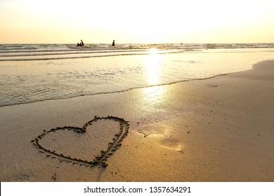 A beach with a heart written on sand