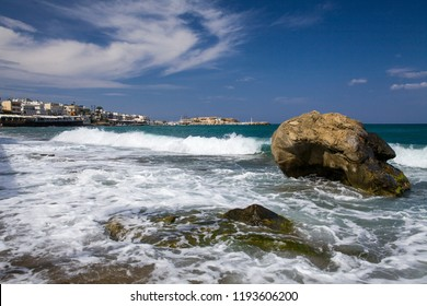 Beach in Hersonissos. Island of Crete in Greece. Blue sea and rock on the background of the city.