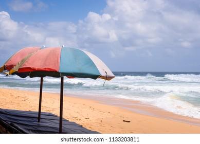 Beach in Hikkaduwa, Sri Lanka. Tropical beach with great waves for surfing. Two beach umbrellas with sun beds on beach in Hikkaduwa, Sri Lanka.