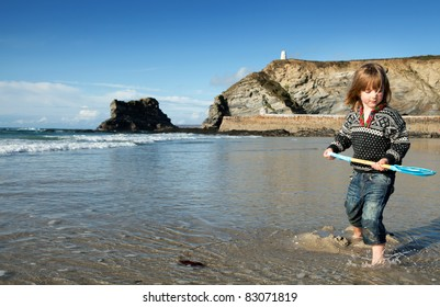 Beach holiday in Cornwall, England. St Agnes coastline with child in water with spade or shovel