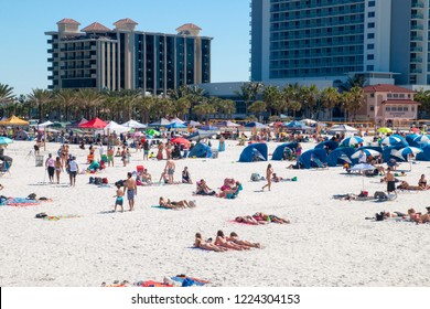 Beach holiday destination scene, crowded tropical sandy beach of Clearwater beach Florida, people sun tanning, relaxing and having fun on the beach, holiday hotel resorts on background