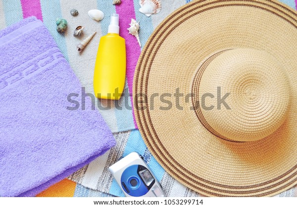 Beach holiday flat lay summer background. Sun hat, purple towel, yellow sunscreen bottle, camera, sunscreen bottle and sea shells. Top view essentials photography