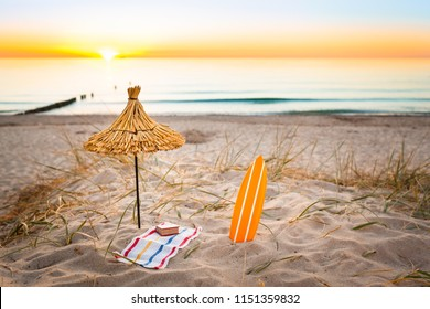 Beach holiday lifestyle miniatures (straw sunshade, surfboard, towel, book) at beautiful sunset background (copy space)