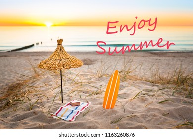 Beach holiday lifestyle miniatures (straw sunshade, surfboard, towel, book) at beautiful sunset background and textual message - Enjoy Summer (copy space)/Beach Idyll Postcard Picture
