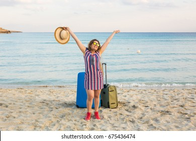 Beach, Holiday, Vacation and Happiness Concept - young smiling woman near the sea with her luggage