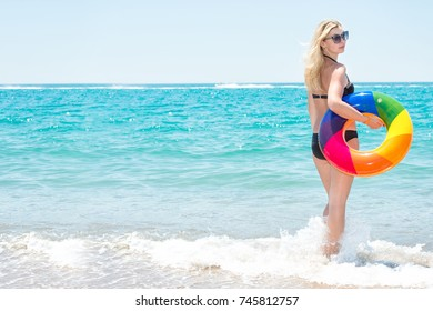 A beach holiday.Beautiful sexy woman in bikini with inflatable circle looks out to sea.
