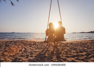beach holidays for romantic young couple, honeymoon vacations, silhouettes of man and woman sitting together on swing and enjoying sunset