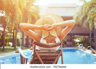 beach holidays and travel, relaxation in luxurious hotel, young happy woman tourist resting near swimming pool