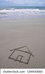 Beach house concept. House drawn in the sand with ocean in background.