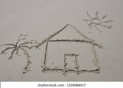 Beach house / dream home concept drawn in the sand.