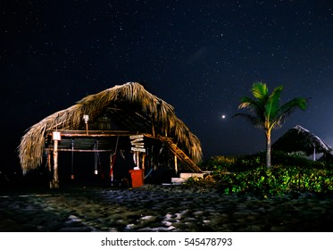 Beach house at ocean shore against the background of stars