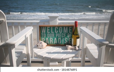 Beach house porch overlooking ocean with two chairs in white with a bottle of wine seashells and paradise sign.