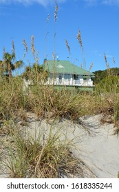 A beach house as viewed though the dunes and sea oats.